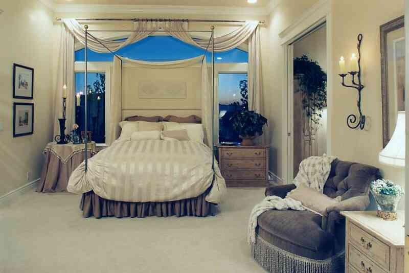 Old-fashion-bedroom-with-light-bed-cover-canopy-bed-and-windows